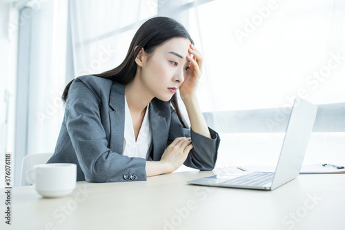 Tablou Canvas business woman Sad and worried working with a laptop in an office,hard work conc