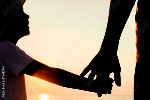 A Hands of happy father and child by the sea on nature silhouette travel Wallpaper Mural
