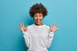 Leinwandbild Motiv Amused pretty girl with curly Afro hair, raises palms, has cheerful expression, smiles broadly, sees something funny, wears white sweater, isolated on blue background. Happy emotions concept