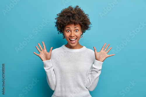 Foto Amused pretty girl with curly Afro hair, raises palms, has cheerful expression, smiles broadly, sees something funny, wears white sweater, isolated on blue background