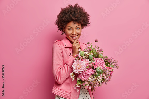 Cheerful tender young Afro American woman being in high spirit, gets pretty flowers, enjoys nice gift, smiles broadly, poses indoor Fototapeta