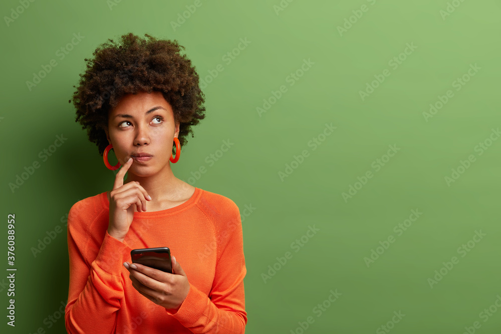 Fototapeta Photo of pretty ethnic woman ponders on how to answer question, thinks deeply about something, uses modern mobile phone, tries to made up good message, keeps index finger near lips, stands indoor
