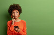 Photo of pretty ethnic woman ponders on how to answer question, thinks deeply about something, uses modern mobile phone, tries to made up good message, keeps index finger near lips, stands indoor