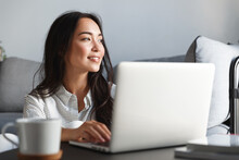 Close-up Of Ambitious Beautiful Asian Female Employee Working From Home. Girl On Remote Using Laptop, Smiling Dreamy While Looking Outside Window. Student Feel Inspired Writing Essay