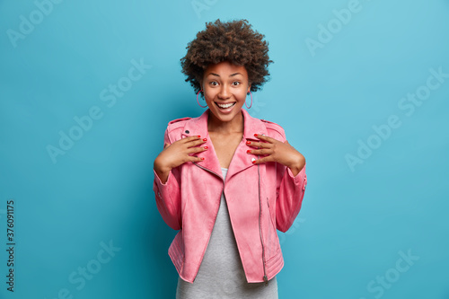 Obraz na plátne Half length shot of pretty cheerful Afro American girl dressed in fashionable pink jacket, smiles broadly, hears exciting good news, poses against blue background
