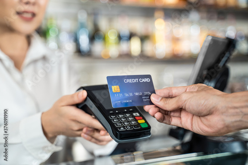 Fototapeta Customer using credit card for payment at cashier in cafe restaurant. obraz