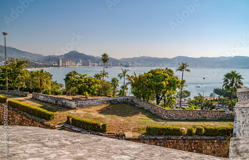 Acapulco, Mexico - November 25, 2008: Ramparts of Fort, Fuerte de San Diego, AKA Museo Historico, looks over bay with mountains and high rise buildings on horizon Wallpaper Mural