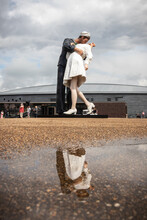 A Statue Of A Sailor Kissing A Girl Located In Portsmouth Dockyard, Replicating The Famous Photo Taken In Time Square At The End Of World War Two Reflecting In A Puddle
