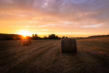 Sunset Over A Field Of Hay Bales