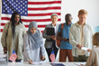 Multi-ethnic group of people registering at polling station decorated with American flags on election day, focus on Arab woman signing ballot form in foreground, copy space