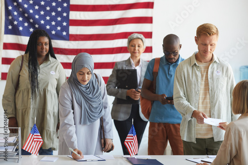 Fotografie, Obraz Multi-ethnic group of people registering at polling station decorated with Ameri
