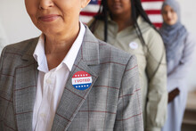 Cropped Image Of Multi-ethnic Group Of People At Polling Station On Election Day, Focus On Smiling Senior Woman With I VOTED Sticker In Foreground, Copy Space