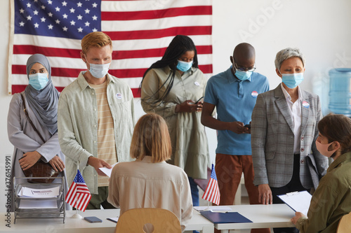Fototapeta Multi-ethnic group of people standing in row and wearing masks at polling station on election day obraz