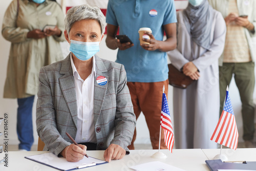 Multi-ethnic group of people standing in row and wearing masks at polling station on election day, focus on modern senior woman looking at camera while registering for voting, copy space
