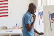 Leinwandbild Motiv Side view portrait of young African-American man standing in voting booth and thinking, copy space