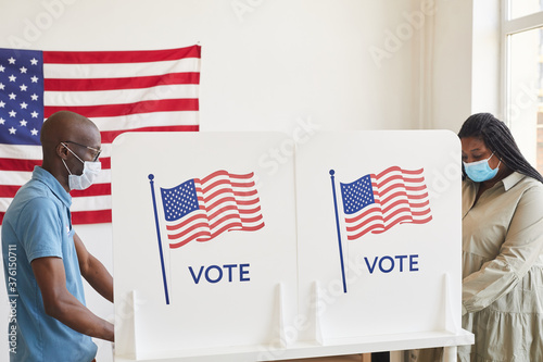 Side view portrait of two African-American people wearing masks standing in voting booths opposite each other on post-pandemic election day, copy space - 376150711