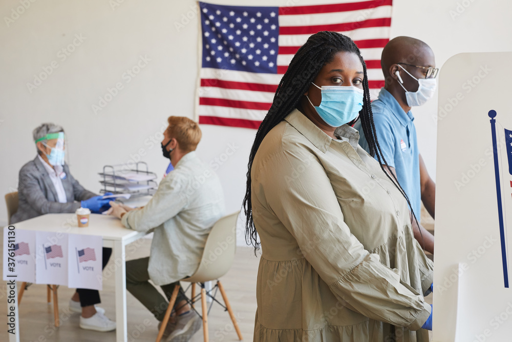 Leinwandbild Motiv - Seventyfour : Side view portrait of female African-American voter standing in booth and looking at camera on post-pandemic election day, copy space