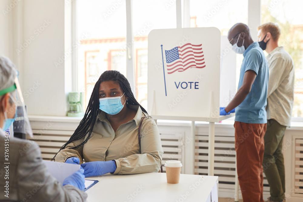 Leinwandbild Motiv - Seventyfour : Multi-ethnic group of people wearing masks voting at polling station on post-pandemic election day, copy space