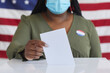 Leinwandbild Motiv Close up of African-American woman wearing mask putting vote bulletin in ballot box and looking at camera while standing against American flag on election day, copy space