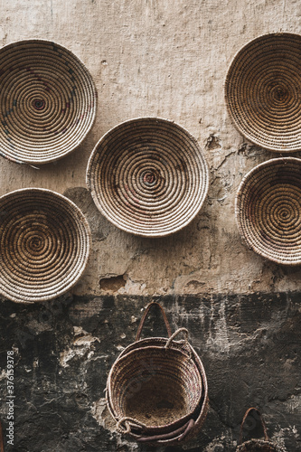 Handmade wicker round baskets hanging on textured wall in Marrakech medina souk. Traditional moroccan manufacture. Grand Bazaar.