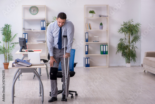 Fototapety, obrazy: Young leg injured employee working in the office