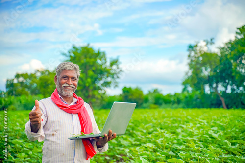 Tablou Canvas Indian farmer using a laptop at agriculture field