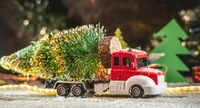 A Red And White Toy Truck Is Transporting A Christmas Tree Against A Background Of Lights And Paper Pines And Snow