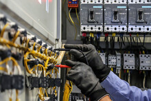 Electrical Engineer Using Digital Multi-meter Is Measuring Equipment To Checking Electric Current Voltage At Circuit Breaker And Cable Wiring System In Main Power Distribution Board.