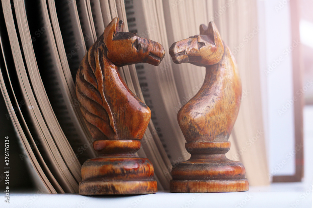 Fototapeta Two wooden horses chess and a book, retro