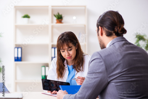 Fotografija Young female doctor and sick businessman in the office