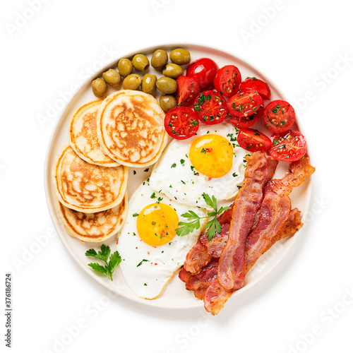 Fototapeta American breakfast with two fried eggs,pancakes,tomato salad,bacon and green olives. isolated on white background. top view obraz