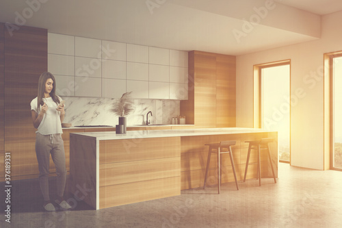 Woman in wooden kitchen with bar