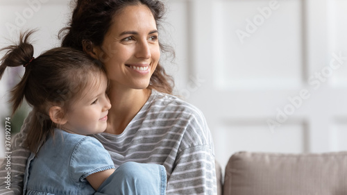 Mom hug little adorable daughter sit on sofa looking away Canvas