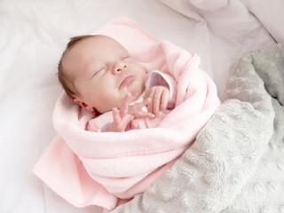 Słodkie niemowlę ułożone do snu. Chwile przed zaśnięciem zamknięte oczka.