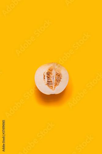 Fototapeta Ripe yellow half of a melon on a yellow background, vertical photo