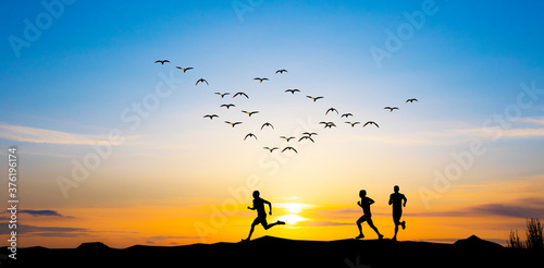 siluetas de unas personas corriendo por el campo