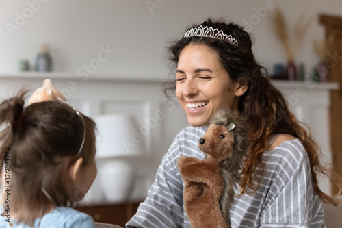 Mom sit on couch wear crown play with small infant daughter at home. Caring smiling mother having fun with hedgehog toy involve in game kid enjoy together puppet theatre, develop educate child concept