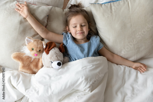 Little daughter with outstretched hands lying in bed with fluffy stuffed toys animal friends cat and teddy bear sleeping in cozy room. Kid girl covered with blanket enjoy healthy night sleep top view