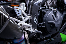 Close Up Of A High Performance Sports Motorcycle With Carbon Enclosing, Looking Onto The Exhaust And Gear Shift Pedals, Motor Engineering