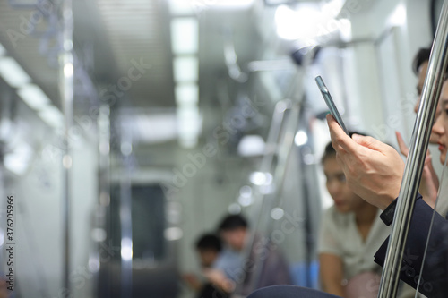 Photo Hand of people holding cellphone while taking metro subway train to work with co