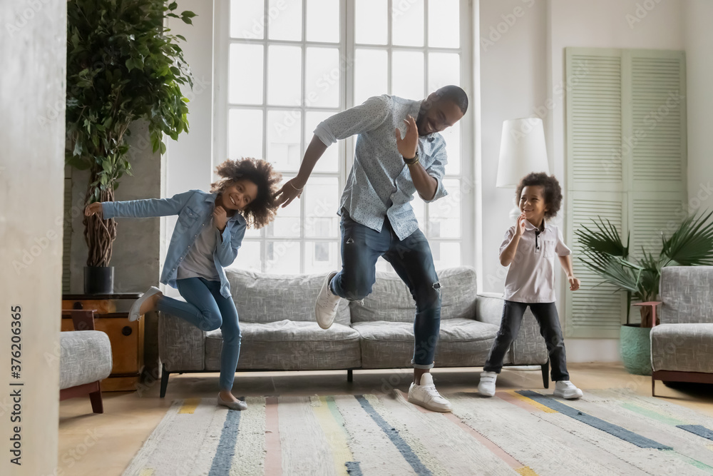 Fototapeta Happy african american father showing funny dancing moves to energetic small children siblings at home. Laughing crazy little biracial boy and girl having fun with caring daddy in living room.