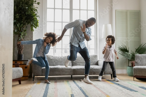 Happy african american father showing funny dancing moves to energetic small children siblings at home Canvas