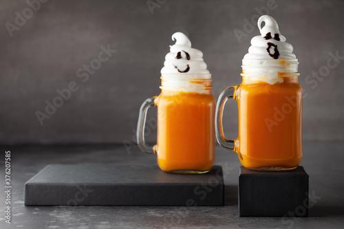 Fototapeta Halloween Pumpkin  cocktail with whipped cream in ghost shape. Freakshake for party. obraz