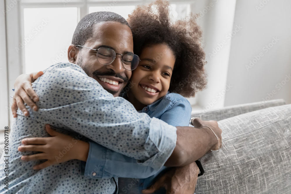 Fototapeta Affectionate loving young african american father cuddling little smiling biracial child daughter, enjoying sweet tender moment together indoors, copy space, happy family showing care and devotion.