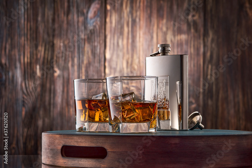 Fotografie, Obraz Two square glasses of whiskey on the rocks and a metal flask stand on a tray against an old wooden wall