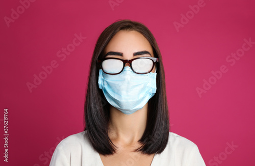 Young woman with foggy glasses caused by wearing disposable mask on pink background Canvas Print