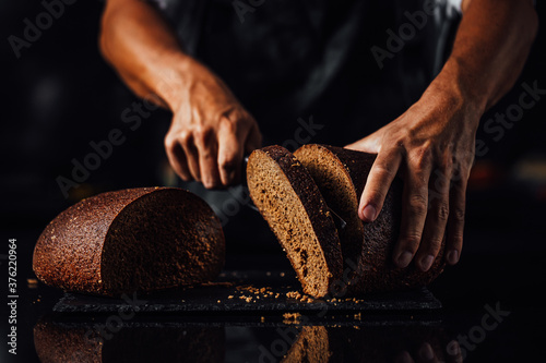 Fototapeta Closeup shot of a man cutting whole grain bread on a stone board background
