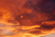 canvas print picture - Dark blood red sky background. Dramatic heavy clouds with the hint of the sun at sunset. Many orange tones and patterns of clouds.