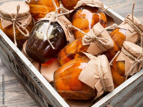Fototapeta Glass jars with orange jam lie in a wooden box obraz