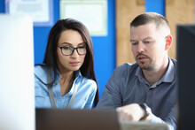 Businesswoman And Businessman Are Sitting At Workplace At Computer And Talking. Small Business Development And Business Development Concept